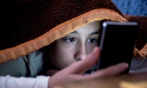 Un preadolescente con lo smartphone sotto le coperte al posto di dormire