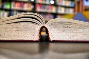 Un grosso libro aperto in biblioteca