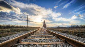 Una ragazza cammina sui binari e sullo sfondo il tramonto
