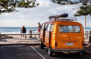 Un van color arancione parcheggiato in riva al mare
