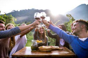 Un gruppo di amici brindano con calici di vino rosso a tavola e sullo sfondo colline
