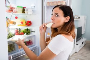 Una giovane donna apre il frigo e mangia la prima cosa che le capita a tiro guardando di non essere scoperta