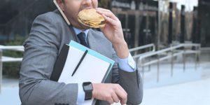 Un uomo stressato dal lavoro mangia di corsa un panino appena fuori dall'ufficio