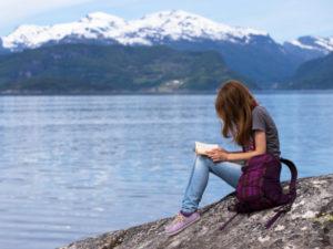 Una ragazza intenta a leggere un libro assegnato come compito per le vacanze e sullo sfondo una montagna innevata che si specchia in un lago blu