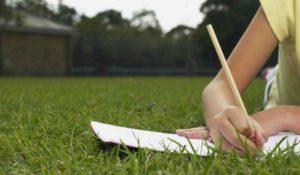 La mano di un ragazzo che fa i compiti delle vacanze con matita e carta appoggiata su un prato verde