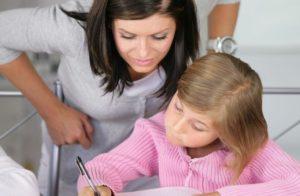 Una mamma sorridente vigila sui compiti delle vacanze della figlia che sta scrivendo sul tavolo di cucina