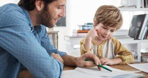 Un papà sorridente aiuta nei compiti delle vacanze il suo bambino seduto al tavolo in cucina