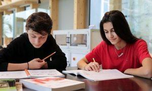 Una ragazza e un ragazzo compagni di scuola fanno insieme i compiti delle vacanze rendendo più gradevole questo impegno