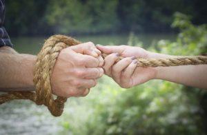 Una mano maschile legata con una corda e tirata o trattenuta da una mano femminile