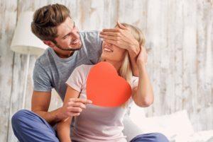 Un giovane uomo felice copre gli occhi alla sua ragazza e le dona un cuore rosso di carta che contiene una sorpresa