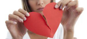 Una giovane donna bionda in primo piano strappa un cuore di carta rossa