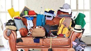 Un divano in pelle carico di oggetti che ha bisogno di decluttering e che le pulizie siano fatte insieme