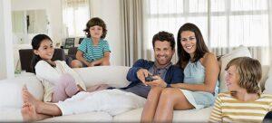 Genitori e figli sereni sul divano dopo aver fatto insieme le pulizie, in un clima minimalista