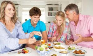 Un papà e una mamma a tavola sereni con i figli adolescenti