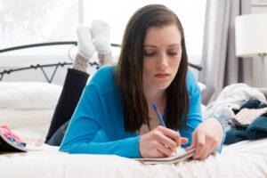 Una ragazza stesa a pancia in giù sul suo letto scrive le sue riflessioni in tempo di pandemia