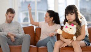 Una bambina col suo peluche in braccio e lo sguardo assente è presente al litigio dei suoi genitori seduti sul divano e con un'alta conflittualità da prevenire