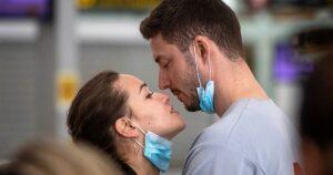 Due giovanni innamorati si abbassano la mascherina e si guardano negli occhi in modo che la conflittualità da prevenire si risolva con la gentilezza