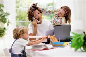 Una mamma vive conflittualità da prevenire essendo in smart working perché lavora da casa col suo computer circondata dai figli che giocano e dal gatto