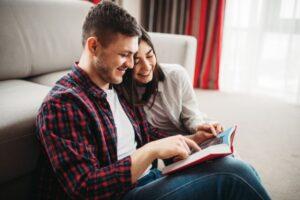 Una coppia sorridente siede a terra nel suo soggiorno e legge insieme un libro durante il lockdown