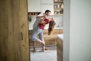 Una giovane coppia balla scalza in cucina durante il lockdown