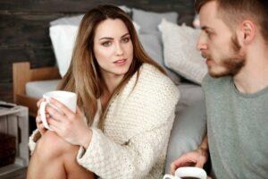 Una giovane coppia dialoga intimamente durante il lockdown tenendo in mano una tazza di caffè
