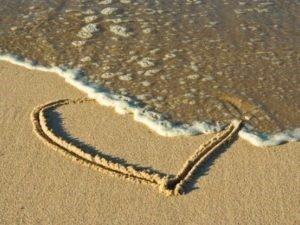 Un cuore tracciato sulla battigia viene cancellato da un'onda