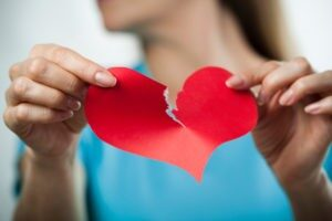 Una ragazza con maglietta azzurra strappa il cuore rosso di carta che ha tra le mani