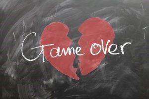 Una lavagna nera con disegnato un cuore rosso spezzato in due e la scritta bianca game over