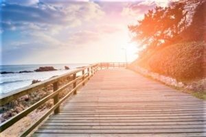 Sul lungo mare e col tramonto all'orizzonte, una strada fatta di assi di legno