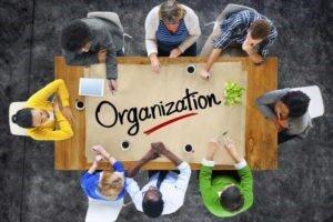Dall'alto un gruppo di persone al lavoro su un tavolo con la grande scritta Organization