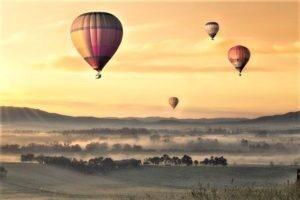 Mongolfiere in cielo e sullo sfondo un'alba rosa