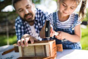 Un papà passa del tempo in giardino con la sua bambina costruendo con legno martello e chiodi