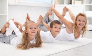 Una mamma passa il tempo con i bambini facendo ginnastica con loro in casa in famiglia in pandemia
