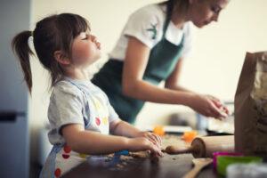 Una mamma con la sua bambina passano tempo assieme cucinando in pandemia