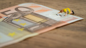 Una donna pulisce in ginocchio una banconota da 50 euro, simbolo di sudditanza economica