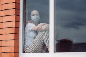 Una giovane donna con mascherina sta alla finestra simbolo del covid e della violenza fisica sulle donne