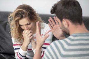 Un uomo di spalle discute animatamente con una donna affranta ed esercita violenza psicologica