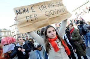 """In una manifestazione giovanile una ragazza porta il cartello """"non è un paese per giovani"""""""