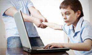 Un ragazzino dipendente da internet e un adulto che tenta di tirarlo via dal computer