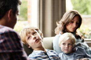 Un papà e una mamma sul divano con i loro due bambini insegnano a scegliere guidandoli