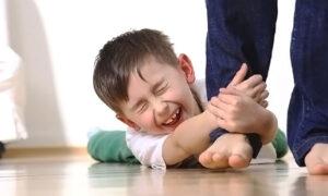Un bambino fa capricci strisciando a terra e afferrando la gamba di un adulto