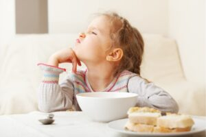 Una bambina seduta a tavola davanti alla sua tazza avanza pretese capricciose