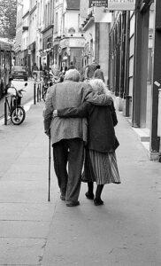 Un uomo ed una donna anziani di spalle camminano insieme sorreggendosi l'un l'altra