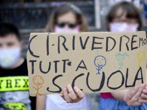 Una ragazzina con masherina e cartello per il mancato ultimo giorno di scuola del 2020