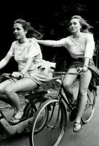 Una ragazza in motorino ne traina un'altra in bicicletta gambe al vento nell'ultimo giorno di scuola degli anni 80