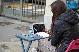 Una ragazza stanca della dad segue le lezioni con computer e tavolino fuori dalla scuola