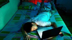 Un ragazzo steso sul letto dorme col computer davanti agli occhi ancora acceso