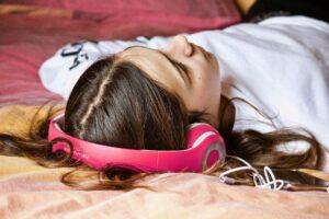 Una ragazza stesa sul letto ascolta musica con le cuffie