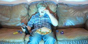 Un ragazzino seduto in divano davanti alla tv mangia da solo voracemente e inconsapevolmente quindi ingrassando