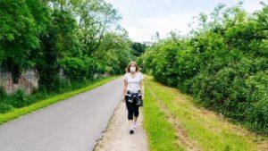 Una donna cammina da sola all'aperto con la mascherina per contrastare la pandemic fatigue